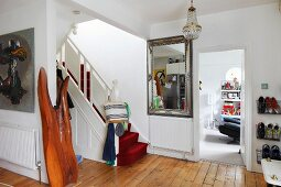 Red carpet on staircase in traditional foyer with wooden floor