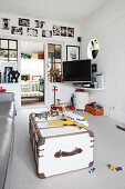 White-painted, vintage trunk and toys on pale grey carpet in living room with open door and view of traditional bench