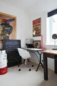 Swivel office chair at vintage console table with marble top in corner and pictures on wall