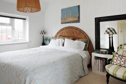 Traditional bedspread on double bed with semicircular wooden headboard in simple bedroom