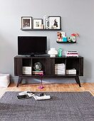 TV on retro-style media cabinet below pictures on narrow floating shelves