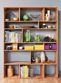 Ornaments and books on exotic wood shelving with compartments of various sizes
