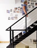Photos pinned on wall alongside black-painted steel staircase; man climbing stairs