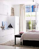White wardrobes, bed and bedroom bench on flokati rug in front of open balcony doors