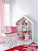 Toys arranged in romantic dolls' house and pink retro dolls' pram