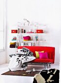 Black and white bed linen on red futon sofa bed in front of colour-coordinated decor on open shelving