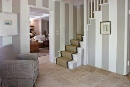 Walls with wide stripes and stone flags in classic foyer with foot of stairs