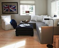 Corner sofa, ottoman and loose-covered armchair in front of framed Union Flag