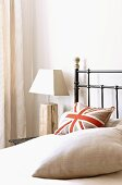Stylised Union Flag cushion on metal bed and bedside lamp with rustic wooden base