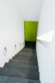 Steep staircase in white stairwell with sconce lamps integrated in wall