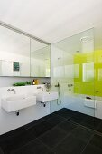 Modern, white bathroom with anthracite tiled floor and lemon yellow wall behind bathtub