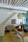 Classic wooden chairs around dining table next to concrete staircase in open-plan interior with wood-beamed ceiling