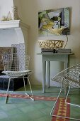 White, wire mesh chairs and small, rustic console table on green tiled floor with border next to open fireplace in living room
