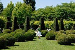In Form von Kugeln und niedrigen Obelisken geschnittene Gehölze in einem Park; gehende Frau in Sommerkleidung