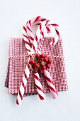 Candy canes and holly berries on napkin