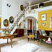 Art collection and antique furniture in London artist's apartment with ladder-style staircase leading to mezzanine