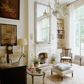 Seating area in front of fireplace with antique furniture and paintings; view into garden