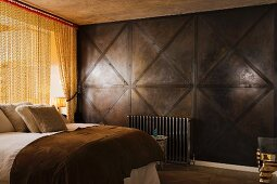 Double bed next to brass-coloured chain curtain and dark, wood-panelled wall in masculine bedroom