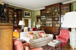 Polstersitzgruppe vor traditionellen Bücherschränken in der Bibliothek eines englischen Landhauses