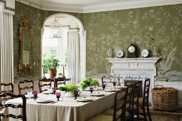 Festlich gedeckter Tisch und Kaminuhr vor floraler Tapete im Esszimmer eines englischen Landhauses