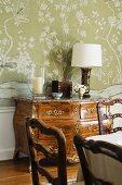 Barocke Kommode vor floraler Tapete und kunsthandwerklich bearbeitete Esszimmerstühle