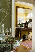 Kostbare Porzellanschale und Kristallkaraffen neben geöffneter Tür mit Blick auf dekorierten Konsolentisch