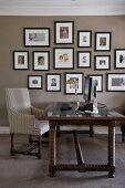 Antiker Schreibtisch mit gedrechselten Beinen aus dunklem Holz vor getönter Wand mit aufgehängter Fotosammlung