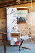 Rustic veranda with delicate spherical lampshade and idiosyncratic stool with metal leg