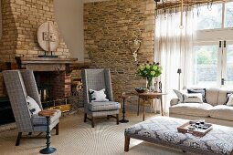 Reading chair in front of open fireplace in interior with enormous window and rustic stone walls