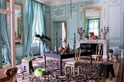 Herrschaftlicher Salon mit bemalter Holzpaneelwand und eingelassenem Spiegel über offenem Kamin, gegenüber Arbeitstisch mit Rokoko Stühlen auf gemustertem Teppich