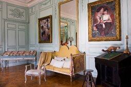 Antike Sitzbank und Kleinmöbel in herrschaftlichem Salon mit Gemälden auf bemalter Holzpaneelwand