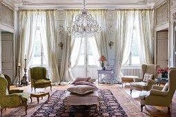 Herrschaftlicher Salon mit Rokoko Sesseln und drapierten Vorhängen vor Fenster und Terrassentür