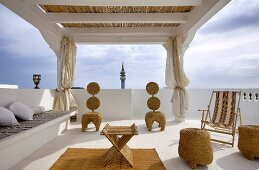 Elegante Dachterrasse mit gerafften Vorhängen und Pergola über Geflechtmöbel auf weissem Boden mit Sisalläufer und gemauerte Bank an Steinbrüstung mit Kissen