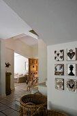 Vorraum mit grossen Weidenkörben auf Boden neben Bilderwand, im Hintergrund Hund vor Durchgang zum Wohnzimmer