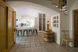 Holzschrank im Durchgang mit breitem Rundbogen zur Küche