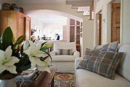 Kissen mit kariertem Bezug auf Polstersofa neben Sessel und Blick durch breiten Rundbogen in die Küche