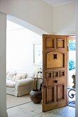 Vorraum mit offener Haustür aus geschnitztem Holz und Blick durch Rundbogen auf weisses Polstersofa