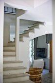 Blick vom Vorraum auf Wendeltreppe in offenem Treppenhaus und weisser Sessel im Durchgang
