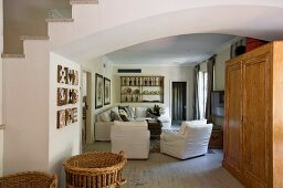Blick durch breiten Rundbogen auf Holzschrank vor weissen Sesseln im Loungebereich