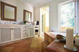 Grossräumiges Bad mit Waschtisch und Unterschränken auf Terrakottaboden gegenüber Badewanne am Fenster