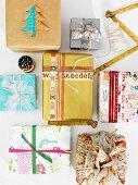 Mit Schrift- und Musterbändern oder Scherenschnitt verzierte und mit ungewöhnlich gemusterten Papieren ideenreich gestaltete Weihnachtspäckchen