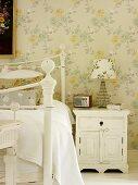 Nachttischchen mit Tischlampe und nostalgischem Radio im romantischen Schlafzimmer