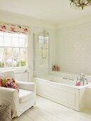 Helles Badezimmer mit Badewanne, weißem Polsterstuhl und weißem Holzboden