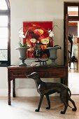 Antiker Wandtisch vor weisser Wand mit modernem Gemälde; davor eine lebensgrosse Windhundfigur aus Bronze