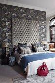 Prunkvolles Bett mit gestepptem, hohen Kopfende an taubenblauer Wandtapete mit floralem Muster; auf dem Bett Zierkissen Ton in Ton mit der Wandtapete