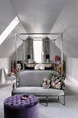 Metall-Himmelbett unter den Dachschrägen mit silbergrauer Couch am Fussende und davorstehendem violetten Polsterhocker