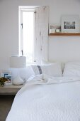 Open window shutter above bed with white bedspread and photos leaning against wall on floating wooden shelf