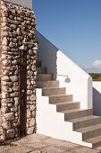 Concrete steps with white balustrade next to outdoor shower on rustic stone wall