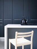Slate grey fitted cupboard doors behind white island counter; vintage kettle on gas hob
