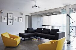 Bright, modern living room with yellow and blue sofa and armchairs; open folding glass doors providing access to balcony